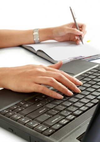 woman write a book and typing her laptop